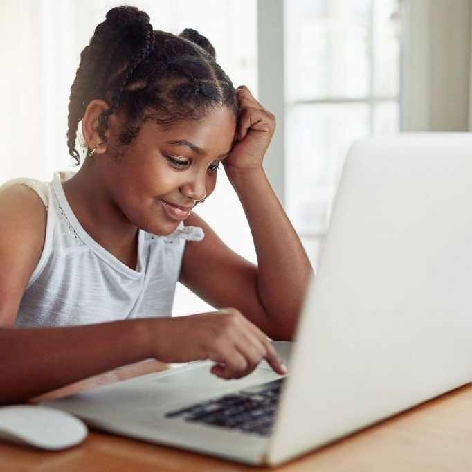 An African-American student works at her white laptop computer.